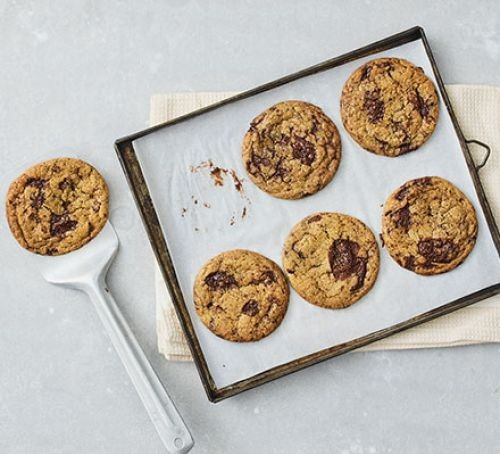 A baking tray with six egg-free chocolate chip cookies
