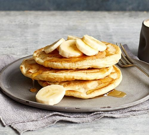 Pancakes on plate with banana and syrup