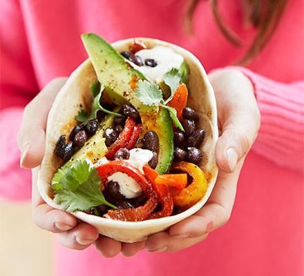 A veggie fajita wrap being held in cupped hands