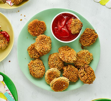 Vegan nuggets on a plate served with a pot of tomato sauce