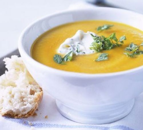 Bowl of vegetable soup topped with herbs and yogurt