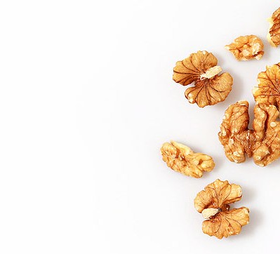 Scattered walnuts on white background