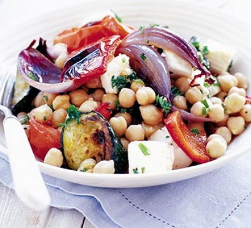 Bowl of chickpea salad with roast onions, tomatoes and feta