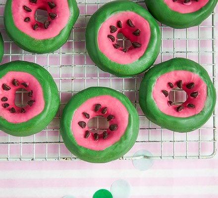 Doughnuts on cooling rack with coloured icing