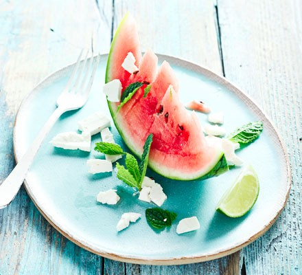 Slice of watermelon with chunks of feta, mint leaves and a wedge of lime