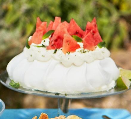 Watermelon, lime and mint sugar pavlova served on a cake stand
