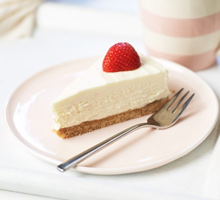 Slice of cheesecake with a strawberry on top, by a fork