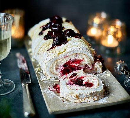 White forest meringue roulade served on a plate and in slices