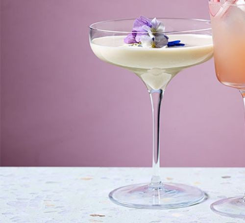 White rabbit cocktail in glass with edible flowers