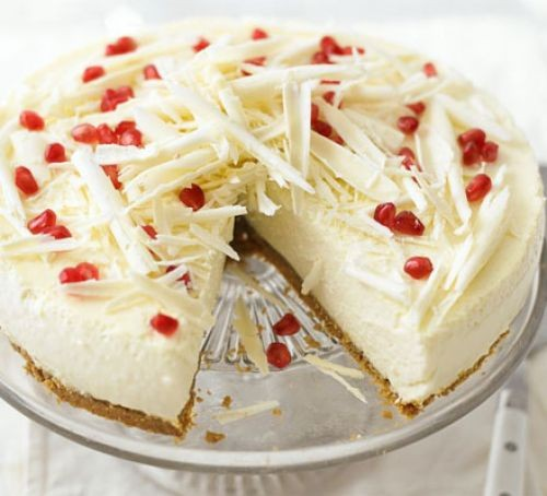 White chocolate cheesecake topped with pomegranates and white chocolate curls