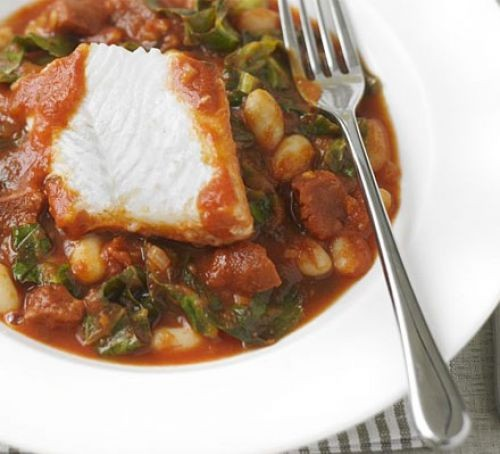 White fish with a bean stew in a bowl with a fork
