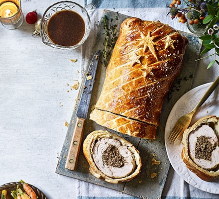 Wild mushroom, port & thyme turkey wellington carved on a serving board
