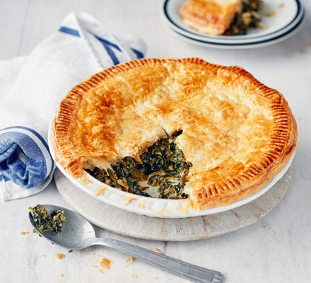 Puff pastry pie with a slice removed to reveal a filling of greens