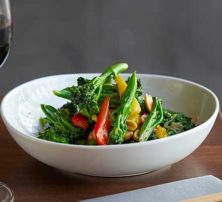 A bowl of wok-fried long-stem broccoli on a wooden table