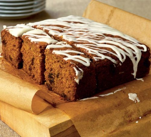 Carrot cake cut into squares with icing drizzle