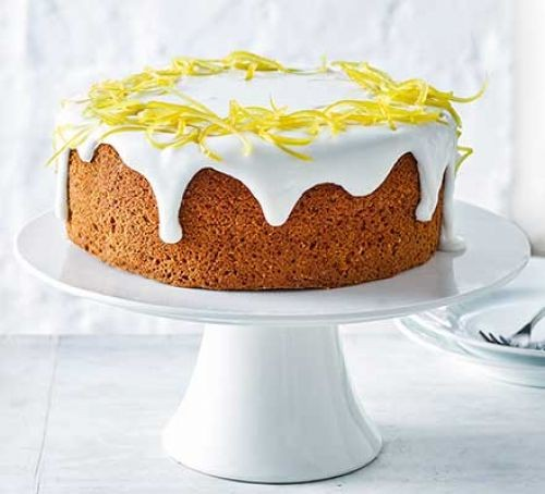 Lemon cake on stand, topped with lemon peel and drizzle icing