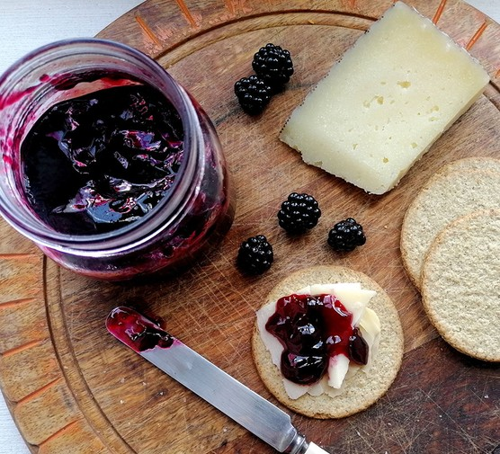 Blackberry jelly in a jar with oatcakes and cheese alongside
