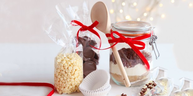 Chocolate cupcake ingredients in jars with wooden spoon