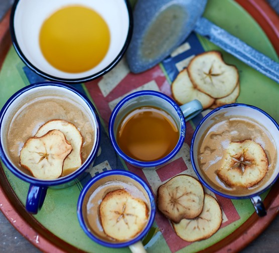 Mugs of apple punch topped with dried apple slices