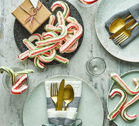 Meringue candy canes on a festive dinner table