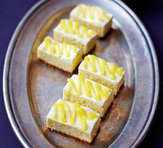 Six mini New York cheesecake bars on an oval tray