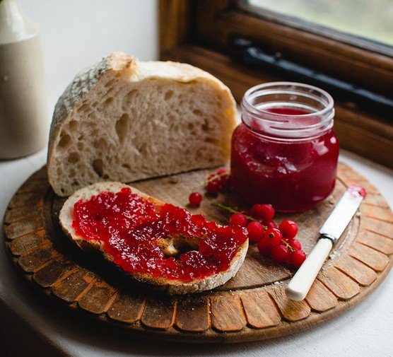 Redcurrant jam in a jar and spread onto a slice of bread