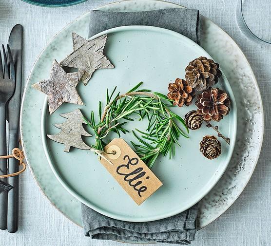 One rosemary wreath place holder on a festive dinner table