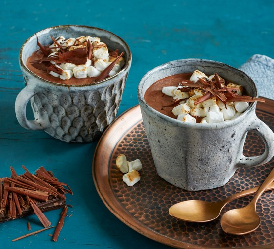 Two mugs of slow cooker hot chocolate topped with marshmallows and chocolate shavings