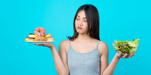 Woman balancing salad in one hand and donuts in the other