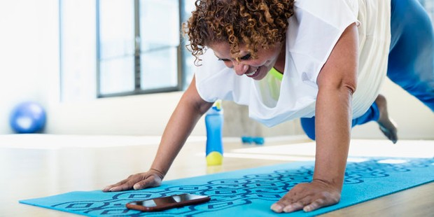 Woman working out on a blue mat at home