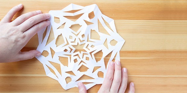 Paper snowflake held down with hands