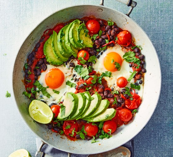 A bowl of eggs with sliced avocados and cherry tomatoes
