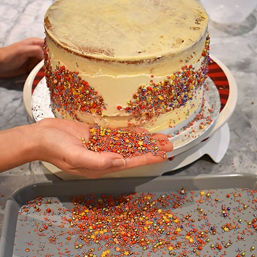 Press the sprinkles onto the band of icing