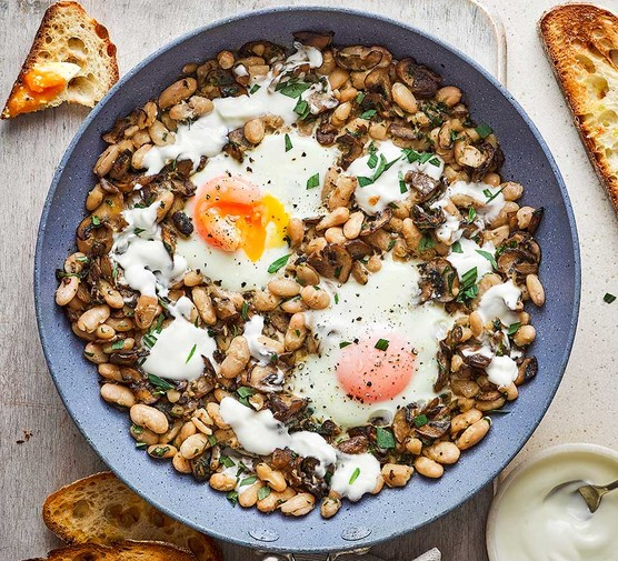 Baked eggs with beans, mushrooms, tarragon and crème fraîche in a frying pan