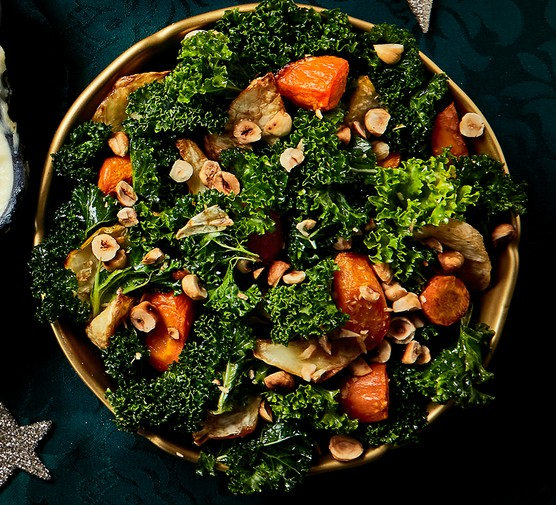 Roasted celeriac & carrots with kale and hazelnuts in a serving dish