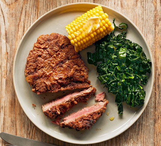 Chicken-fried steak served with corn on the cob and greens