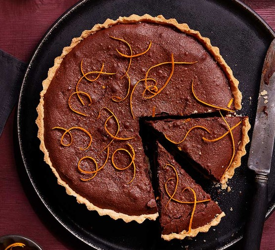 Chocolate orange brownie tart with two slices cut out
