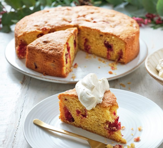 A slice of cranberry and clementine polenta cake with a dollop of zesty cinnamon cream on top