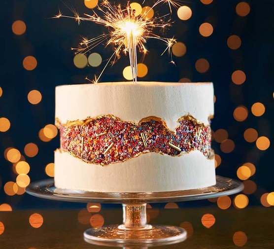 Fault line cake on a cake stand with a sparkler in the centre