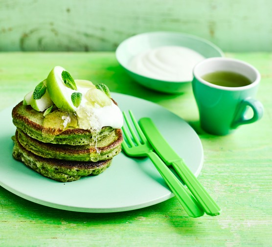 Stack of green match American pancakes with matcha tea and cream
