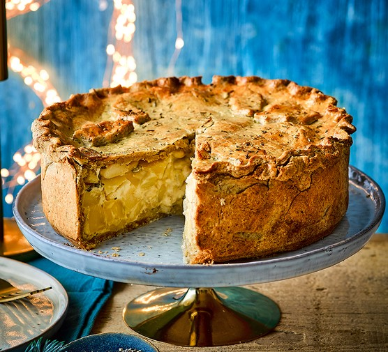 Parsnip, feta & butter bean pie on a cake stand with a slice taken out