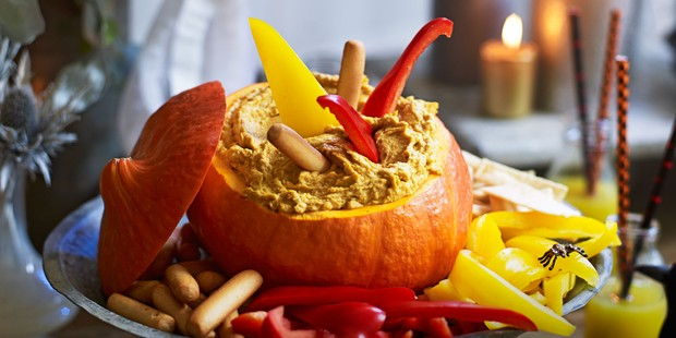 Open pumpkin filled with hummus and peppers