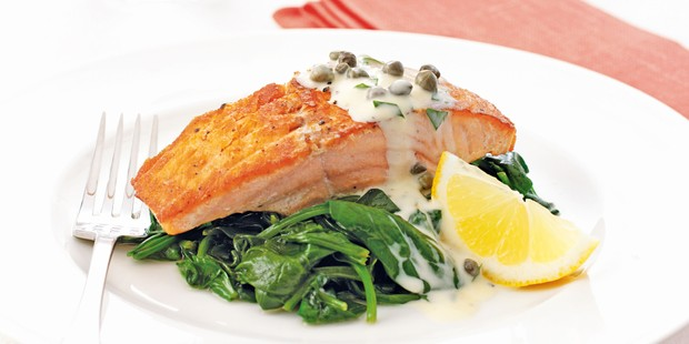 Salmon fillet on a bed of spinach, dressed in tartare sauce, with a lemon wedge
