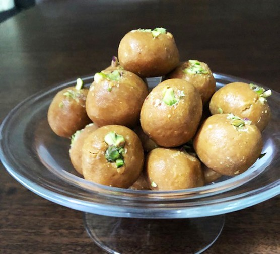 Spiced gram flour ladoo (besan ladoo) served on a cake stand