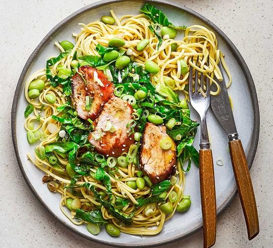 Sticky hoisin pork fillet with sesame greens and noodles served on a plate