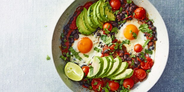 A large bowl full of black beans, sliced avocado, fried eggs and tomatoes