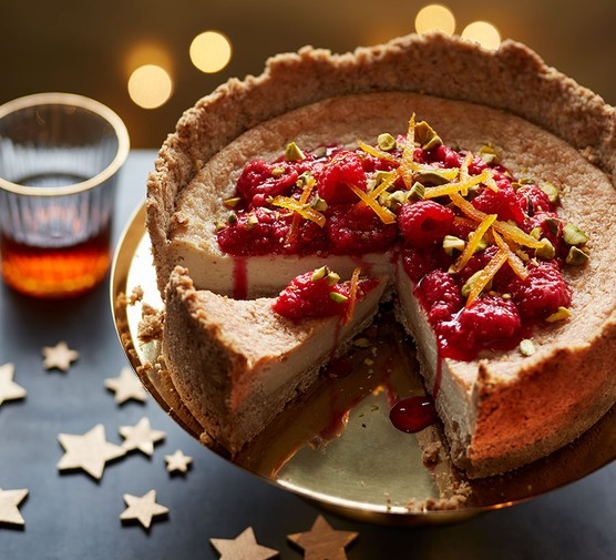 Baked vegan cheesecake with raspberries & clementine served on a cake stand