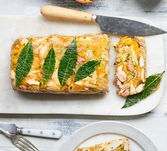 Chicken terrine topped with leaves, net to knife