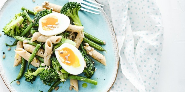 A salad of boiled eggs, pasta and broccoli on a blue plate