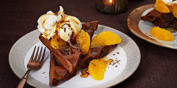 Chocolate waffles topped with cream, clementine segments and chocolate shavings
